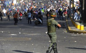 The Voice of Thousands: Students protest in Caracas on February 12, as a National Guards Member holds his ground (america.aljazeera.com)